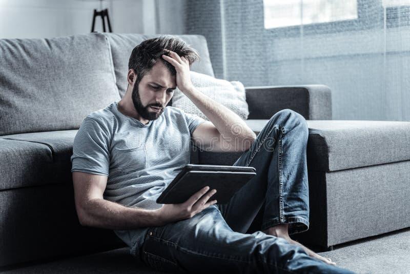 Homem farpado deleitado negativo que tem a dor de cabeça fotos de stock