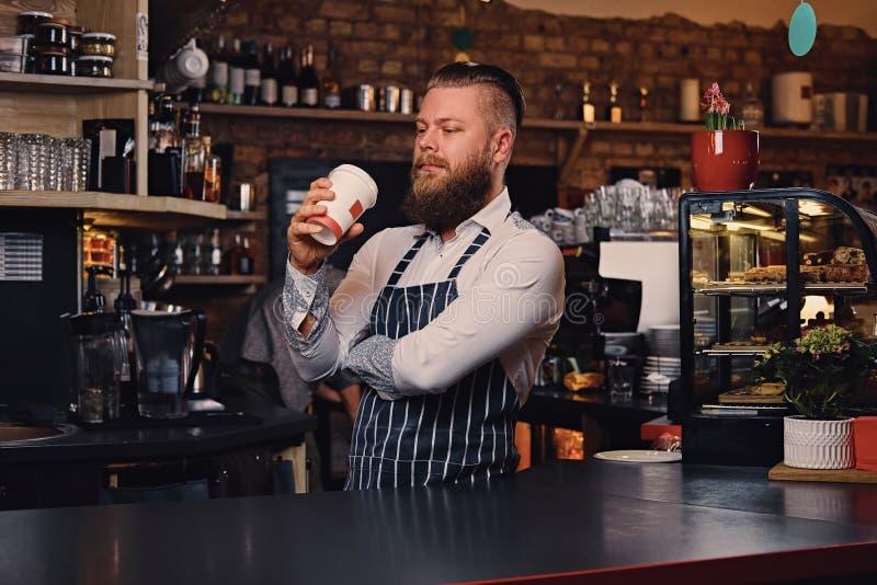 Homem farpado do barista no suporte da barra em uma cafetaria fotografia de stock royalty free