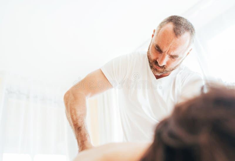 Homem farpado do massagista que faz manipulações da massagem na baixa área traseira durante a massagem Imagem do conceito dos cui imagens de stock royalty free