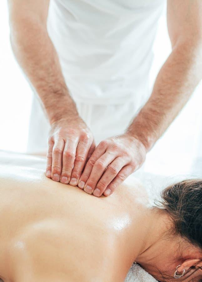 Homem farpado do massagista que faz manipulações da massagem na zona da área da espinha dorsal da espinha durante a massagem nova foto de stock