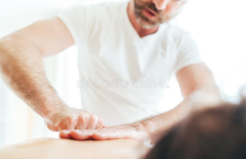 Homem farpado do massagista que faz manipulações da massagem na zona da área da omoplata durante a massagem nova do corpo fêmea fotografia de stock