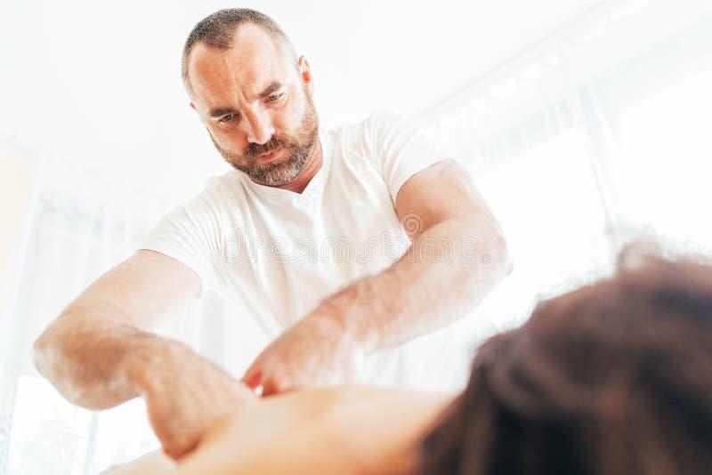 Homem farpado do massagista que faz manipulações da massagem na zona da área da omoplata durante a massagem nova do corpo fêmea C fotografia de stock