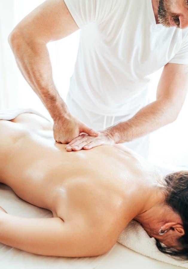 Homem farpado do massagista que faz manipulações da massagem na zona da área da omoplata durante a massagem nova do corpo fêmea foto de stock royalty free