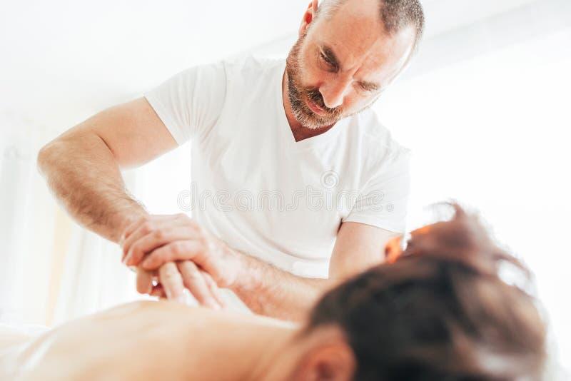 Homem farpado do massagista que faz manipulações da massagem na zona da área da omoplata durante a massagem nova do corpo fêmea imagem de stock