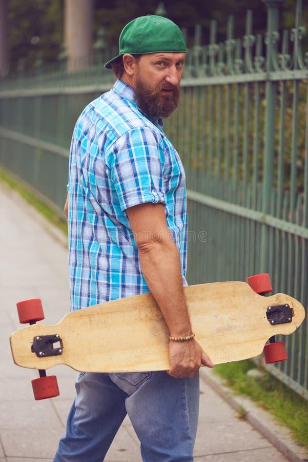 Homem farpado do moderno que levanta com longboard e no tampão verde elegante foto de stock