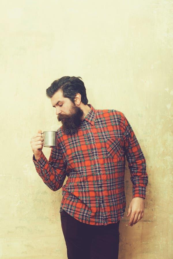 Homem farpado do olhar severo com a barba que guarda a caneca do metal fotografia de stock