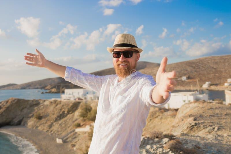 Homem farpado do viajante do moderno do ruivo com mãos abertas no chapéu e nos óculos de sol que sorri contra o fundo azul do mar fotos de stock