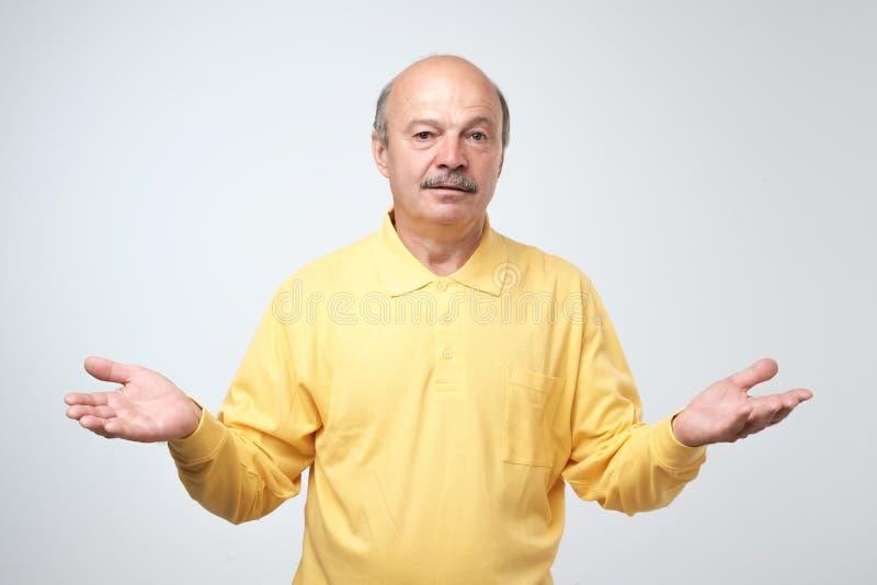 Homem farpado emocional não certo para algo Tiro do estúdio, fundo cinzento foto de stock