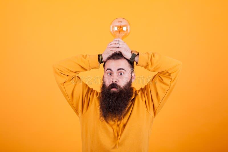 Homem farpado engraçado com uma ampola sobre sua cabeça na parte dianteira sobre o fundo amarelo fotos de stock