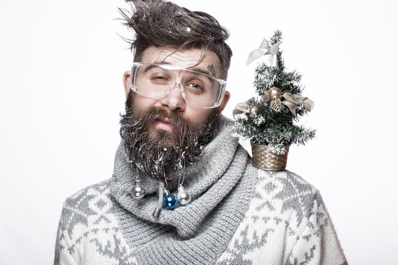 Homem farpado engraçado em uma imagem do ` s do ano novo com neve e decorações em sua barba Festa do Natal fotografia de stock royalty free