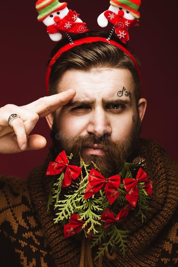 Homem farpado engraçado em uma imagem do ` s do ano novo como Santa Claus com as decorações em sua barba Festa do Natal imagens de stock