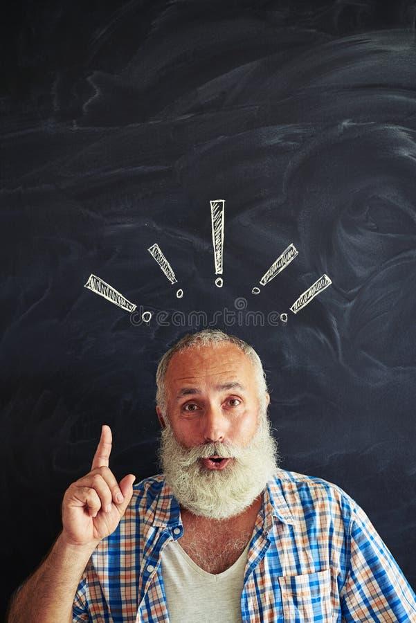 Homem farpado envelhecido entusiasmado contra o quadro-negro da escola que guarda a para imagem de stock royalty free