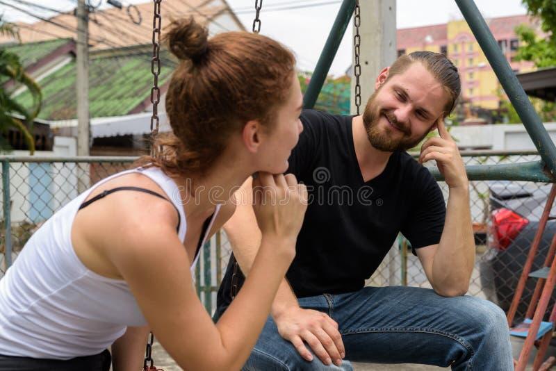 Homem farpado feliz novo que olha o sorriso bonito novo da mulher fotografia de stock