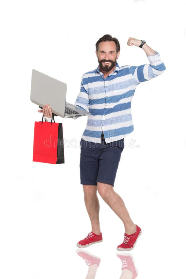 Homem farpado feliz que mostra seus músculos ao estar com portátil fotografia de stock