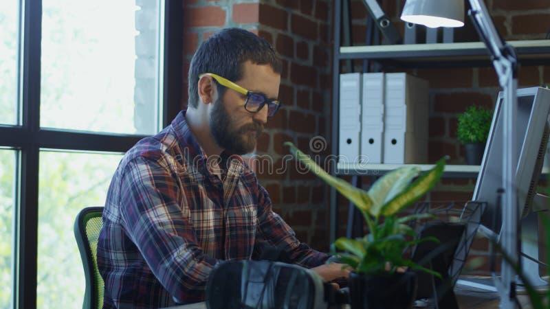 Homem farpado focalizado que usa o computador imagens de stock royalty free