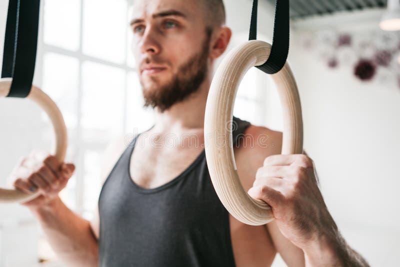 Homem farpado forte que guarda anéis ginásticos no gym foto de stock royalty free