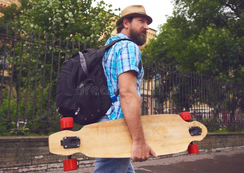 Homem farpado Freaky que anda com longboard imagens de stock