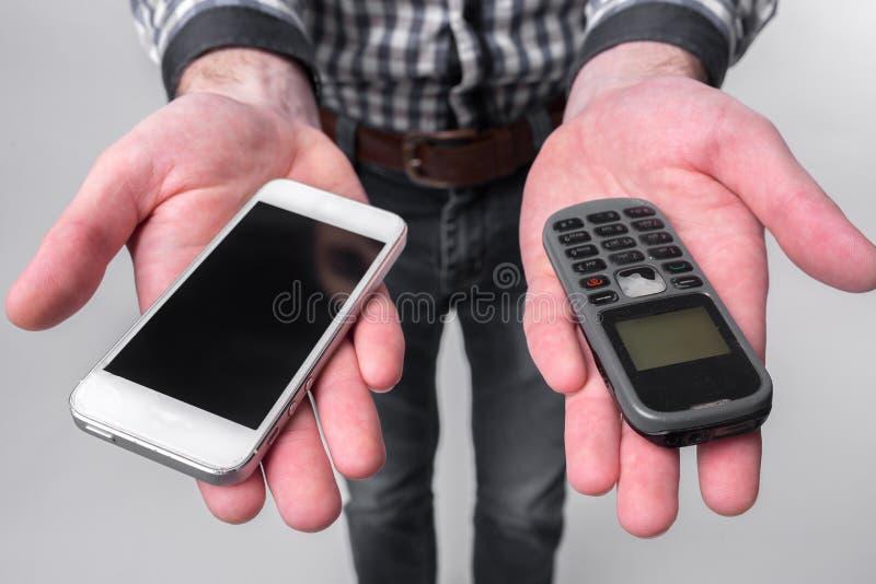 Homem farpado isolado em um fundo claro que guarda um smartphone moderno e um telefone celular velho com botões foto de stock