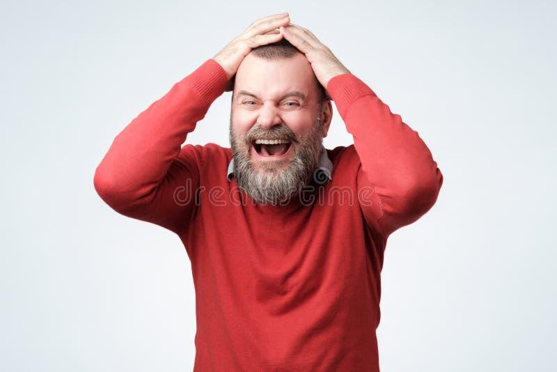 Homem farpado maduro consider?vel no riso vermelho da camiseta imagens de stock