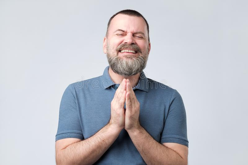 Homem farpado maduro para juntar-se às mãos que imploram junto pedir a ajuda da remissão fotos de stock