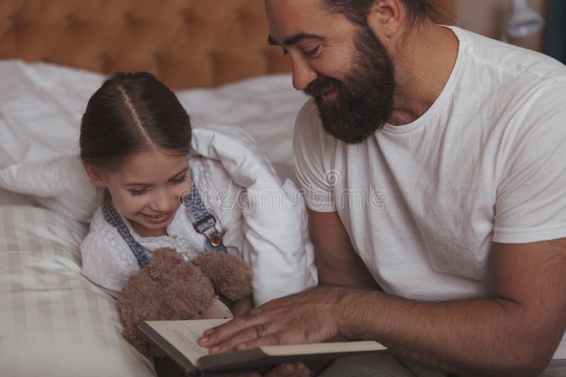 Homem farpado maduro que descansa em casa com sua filha pequena imagens de stock