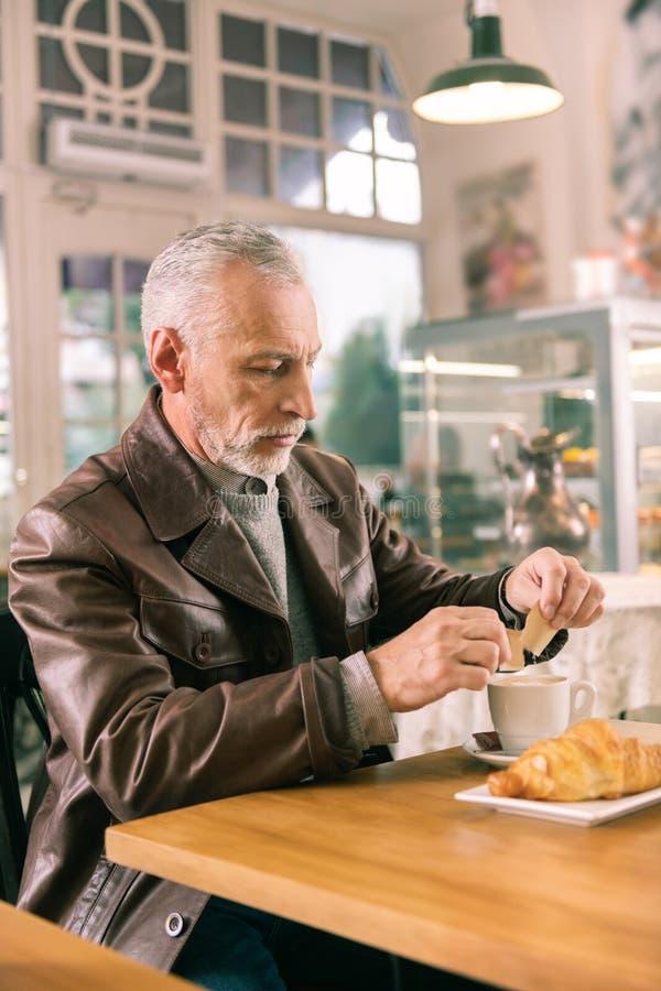 Homem farpado maduro que veste o assento marrom do casaco de cabedal na padaria francesa fotografia de stock royalty free