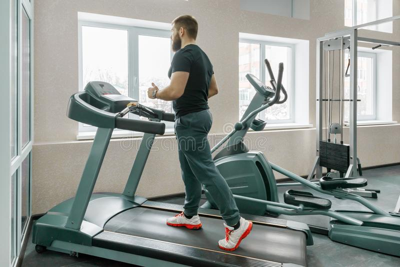 Homem farpado muscular atlético que corre em escadas rolantes no gym moderno do esporte Aptidão, esporte, treinamento, conceito d imagem de stock