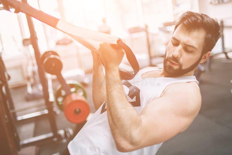 Homem farpado muscular durante o exercício no gym foto de stock