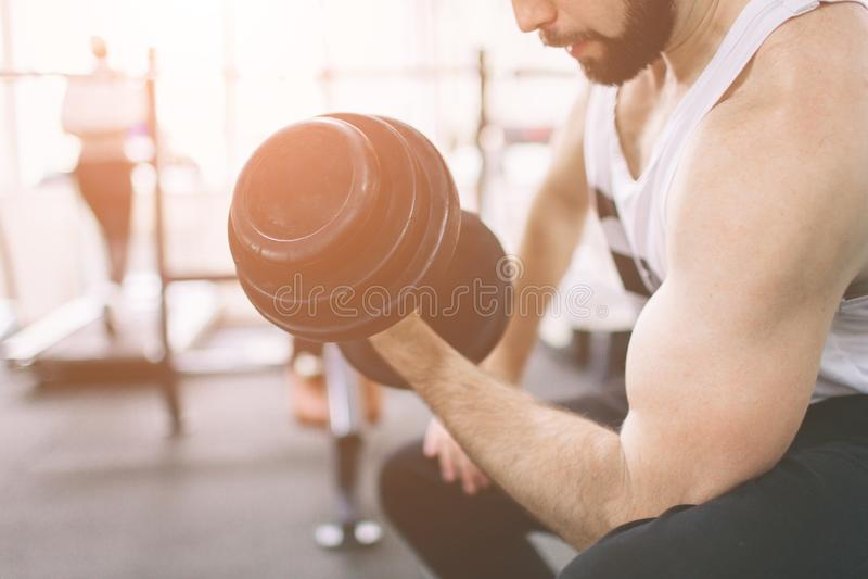 Homem farpado muscular durante o exercício no gym Halterofilista muscular do atleta no bíceps do treinamento do gym com peso fotos de stock