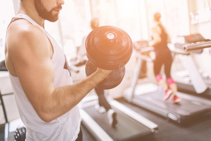 Homem farpado muscular durante o exercício no gym Halterofilista muscular do atleta no bíceps do treinamento do gym com peso imagens de stock royalty free