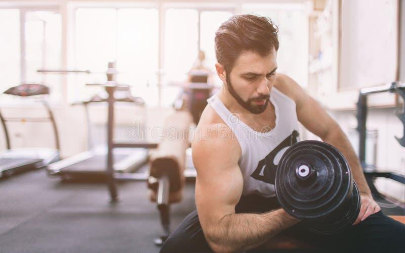 Homem farpado muscular durante o exercício no gym Halterofilista muscular do atleta no bíceps do treinamento do gym com peso fotografia de stock royalty free