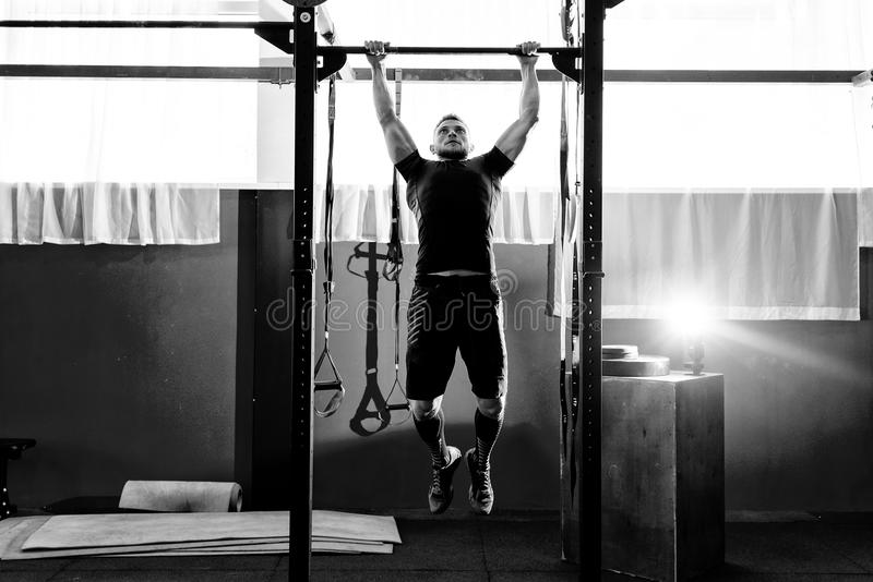 Homem farpado muscular que treina seus bíceps e parte traseira no gym Tra??o-UPS Conceito do estilo de vida do exerc?cio fotos de stock royalty free