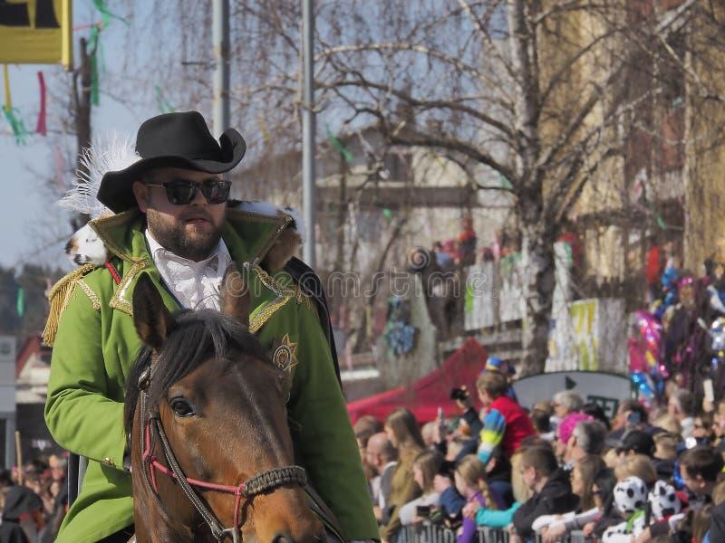 Homem farpado no cavalo dos passeios do revestimento verde imagens de stock