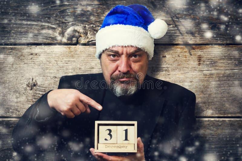 Homem farpado no chapéu de Santa Claus com um calendário de madeira 31th dezembro imagens de stock