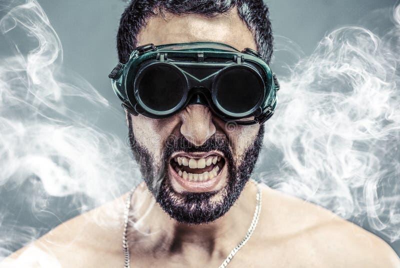 Homem farpado no fumo imagens de stock royalty free