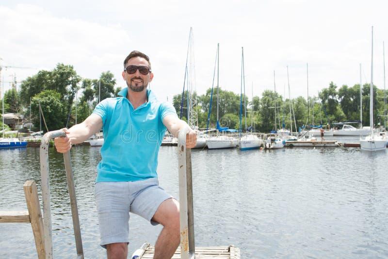 Homem farpado no polo e óculos de sol que laddering acima no barco Homem de negócios feliz em férias com os iate na doca fotos de stock royalty free