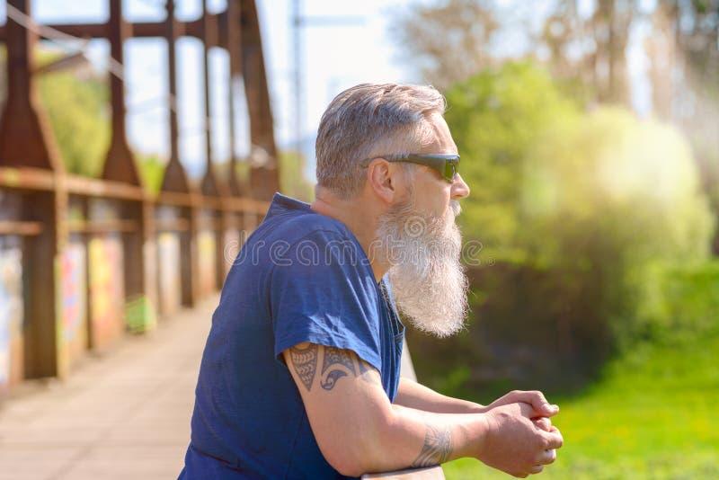 Homem farpado nos óculos de sol que estão em uma ponte foto de stock royalty free