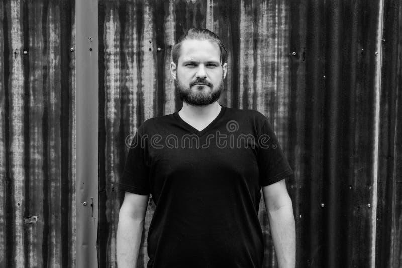 Homem farpado novo com o cabelo amarrado contra a parede oxidada velha da folha dentro fotografia de stock