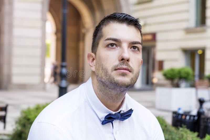 Homem farpado novo considerável com camisa e laço brancos na rua imagens de stock