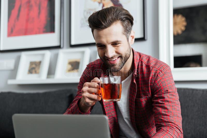 Homem farpado novo feliz que usa o chá bebendo do laptop fotos de stock