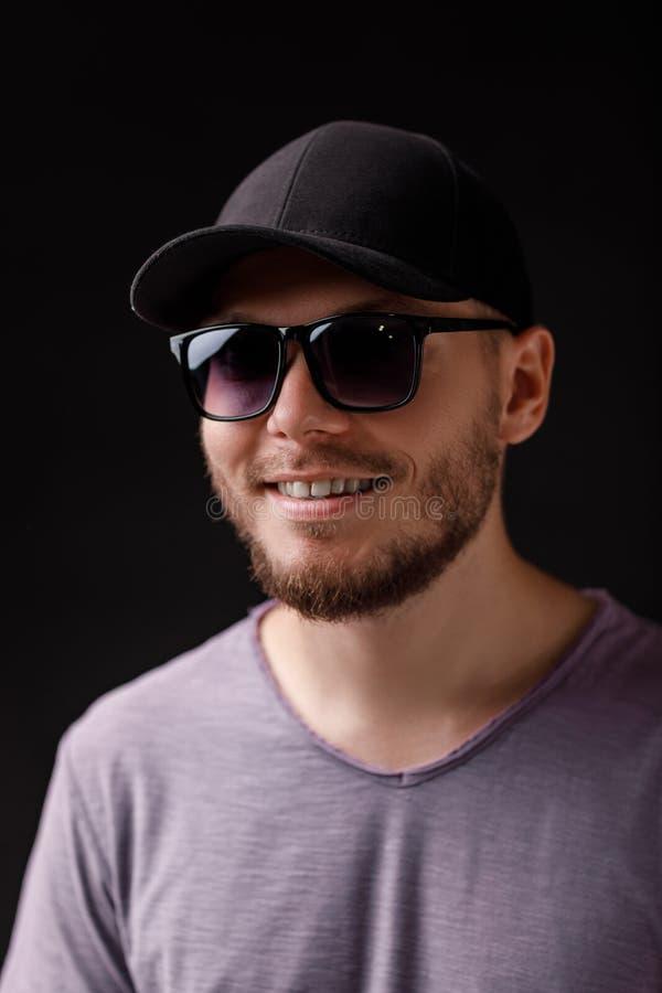 Homem farpado novo no tampão e nos óculos de sol foto de stock