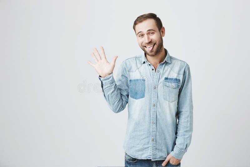 Homem farpado novo positivo considerável na roupa à moda que levanta a mão e que gesticula como se dizendo o olá!, tendo o bom hu foto de stock