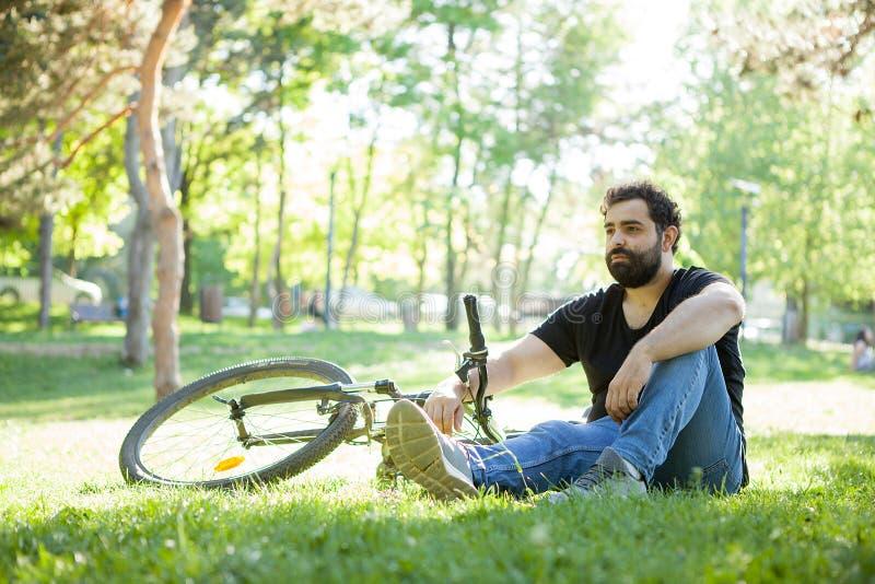 Homem farpado novo que descansa na grama no parque foto de stock royalty free