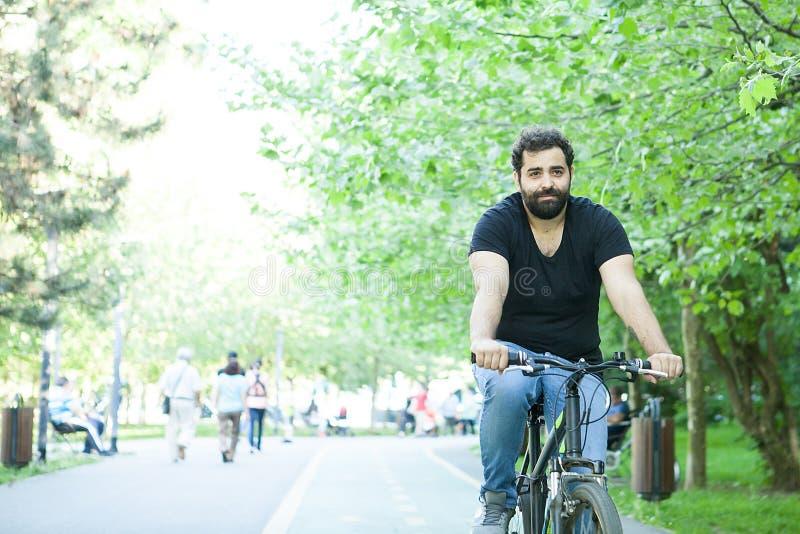 Homem farpado novo que monta uma bicicleta no parque fotografia de stock