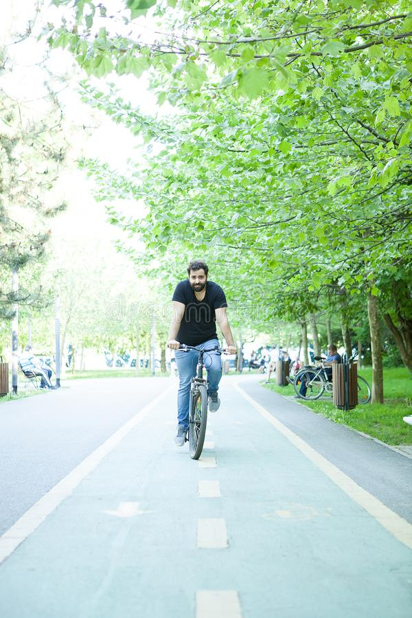 Homem farpado novo que monta uma bicicleta no parque imagens de stock
