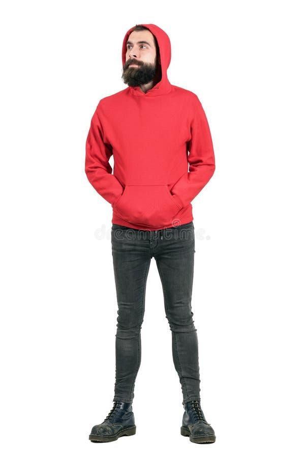 Homem farpado novo que veste o hoodie vermelho com mãos em uns bolsos que olham afastado imagens de stock royalty free