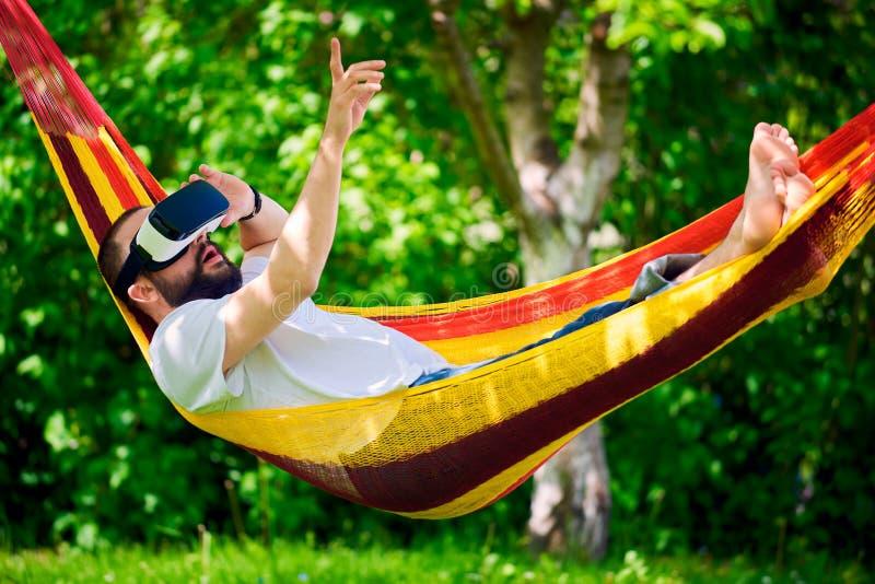 Homem farpado novo que veste os óculos de proteção da realidade virtual que relaxam em uma rede do jardim O divertimento do estil fotografia de stock