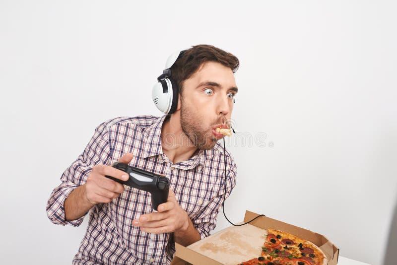 Homem farpado parvo adulto com cabelo escuro curto nos fones de ouvido, jogando jogos onlines no computador pessoal com controlad imagens de stock royalty free