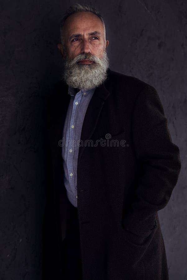 Homem farpado pensativo que olha em algum lugar ao levantar no studi escuro foto de stock royalty free