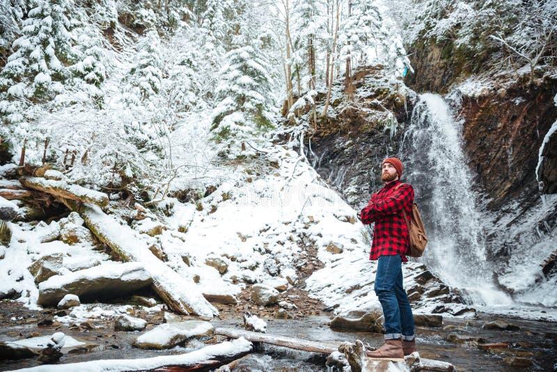 Homem farpado pensativo que stading perto da cachoeira em montanhas no inverno foto de stock